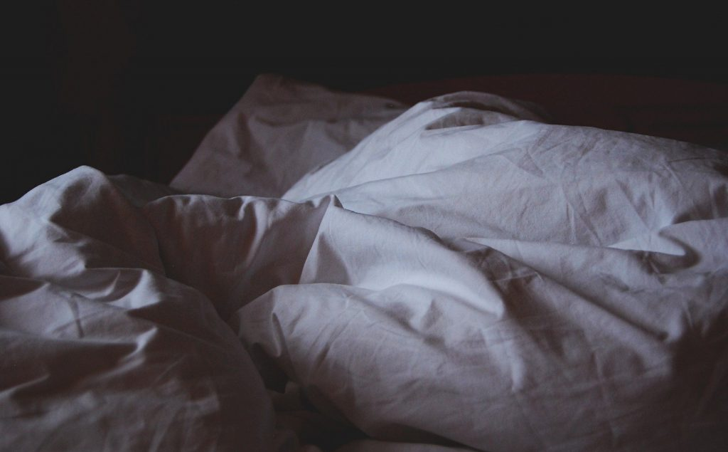 Photo of an unmade bed in shadows