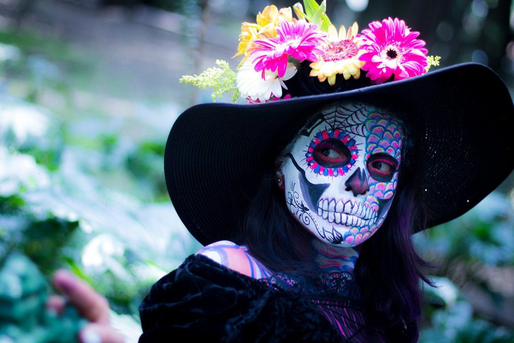 Person painted like a skeleton, wearing a hat decorated with flowers