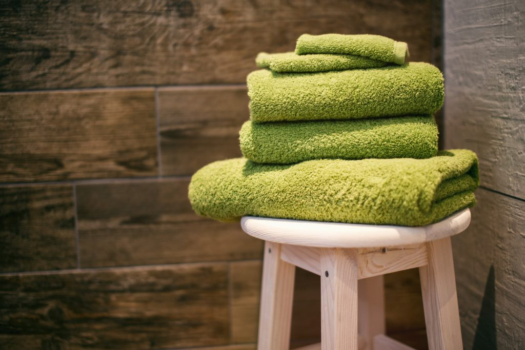 folded green towels on a stool in a sauna