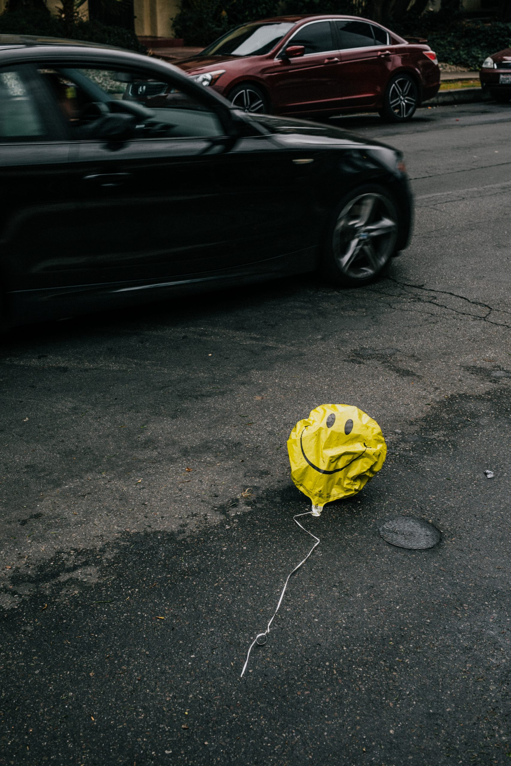 yellow smiley balloon, deflated and on the street