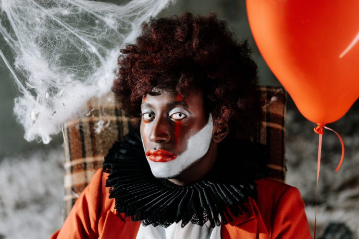 person in clown makeup seated in a tweed-covered armchair side eyes the viewer