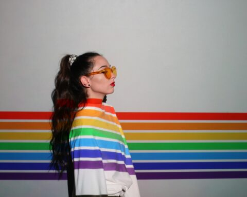 rainbow shines on person turned to the right against a white wall