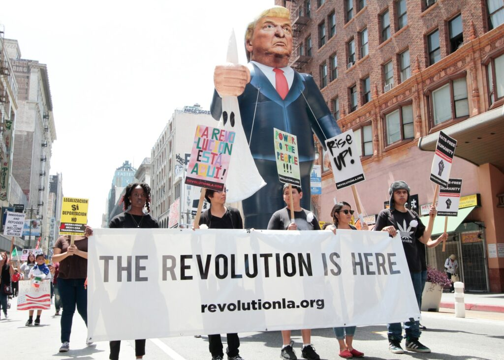 protestors walk with banner and Trump puppet