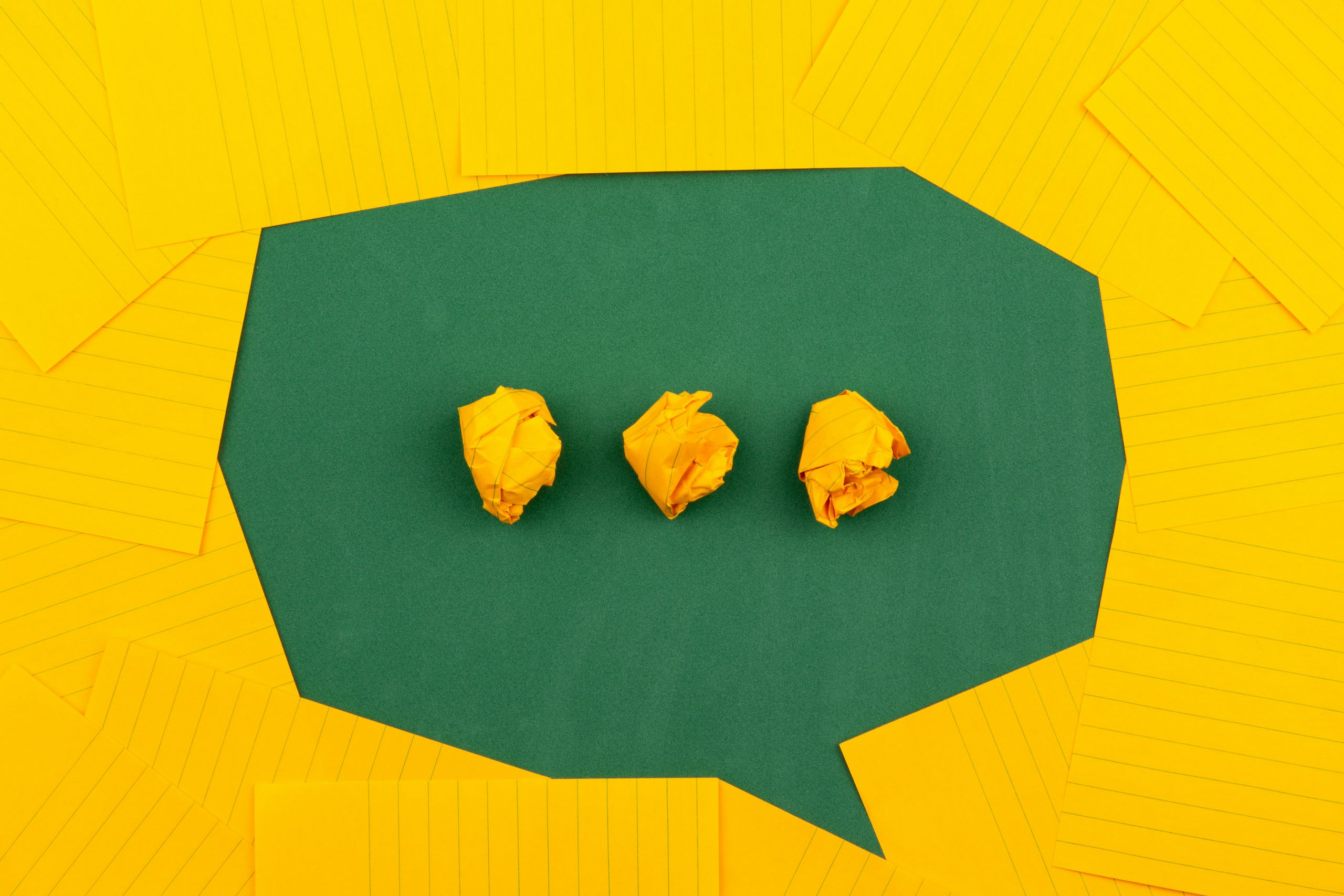 orange sheets of paper lie on a green school board and form a chat bubble with three crumpled papers