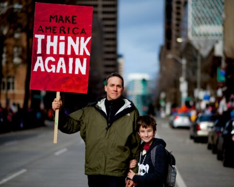 child stands by person holding red and white protest sign